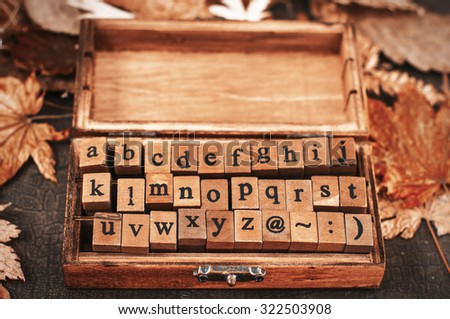 wooden stamps alphabet in old vintage box on autumnal dry maple leaves background