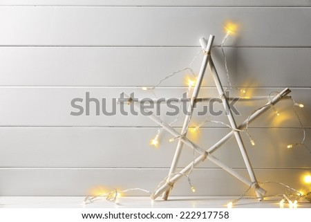 Wooden star with christmas lights on wood background - stock photo