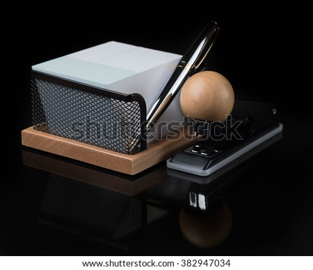 wooden stationery set with silver pen isolated on a dark background - stock photo