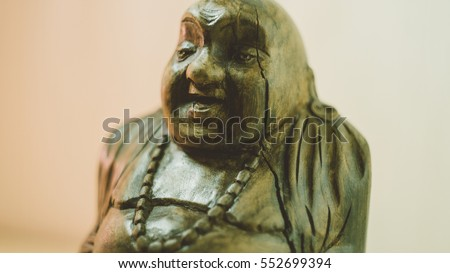 wooden statue laughing Buddha. The character of Chinese Buddhism. Unfocused & Film Texture