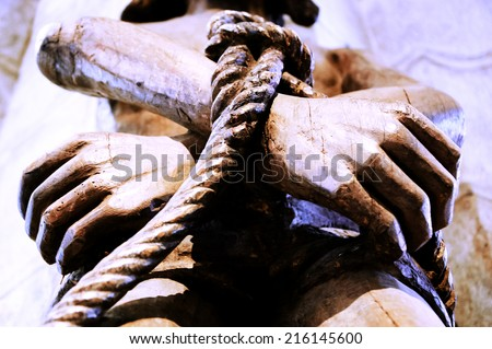 Wooden statue of Jesus with tied hands. Aged photo. - stock photo