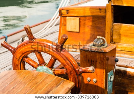 wooden steering wheel and compass on a vintage sailing boat