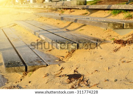 Wooden steps going up in the sand at sunset  - stock photo