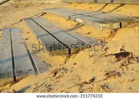 Wooden steps on a sandy beach - stock photo