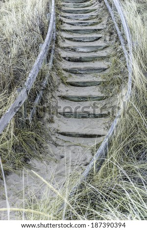 Wooden steps, partly covered with sand, with curved wooden railing at the bottom of a steep but stable dune by Lake Michigan early in spring - stock photo
