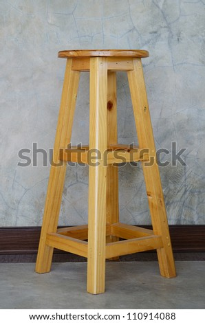 Wooden stool with cement wall. - stock photo