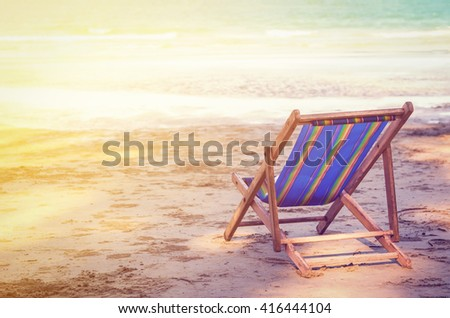 Wooden striped deckchair at ocean sandy beach with sunset light and vintage tone - stock photo