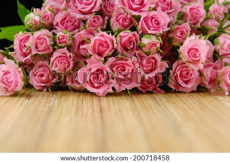 Wooden surface with copy space decorated with bouquet of roses  - stock photo