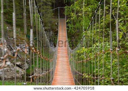 Wooden suspension bridge over the river in the forest - stock photo
