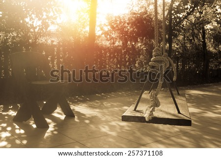 Wooden swing in garden with sunset background. Vintage filter. - stock photo