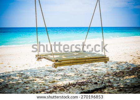 Wooden swing on beautiful white sand tropical beach, Thailand.