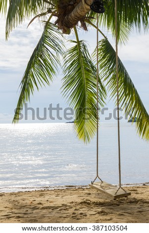wooden swing with coconut palm tree on the beach.