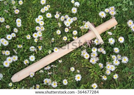 wooden sword lying in the grass and flowers/sword and flowers - stock photo
