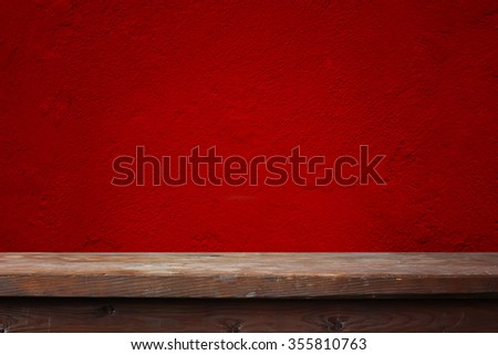 Wooden table against a red wall. A blank space for your text.