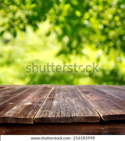wooden table against defocused summer background - stock photo