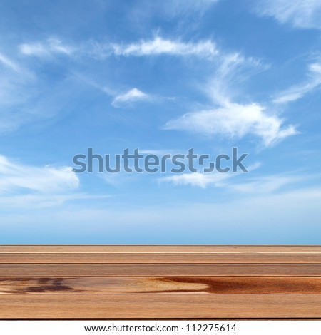 Wooden table and blue sky - stock photo