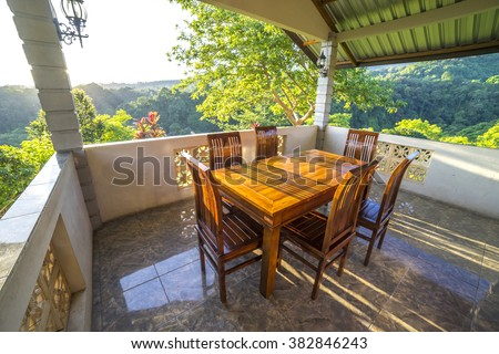 Wooden table and chair at balcony with natural sunlight and tropical view background