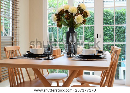 wooden table and chairs in dining room with elegant table setting - stock photo