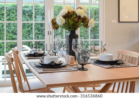 wooden table and chairs in dining room with elegant table setting
