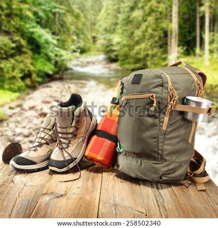 wooden table backpack and shoes  - stock photo