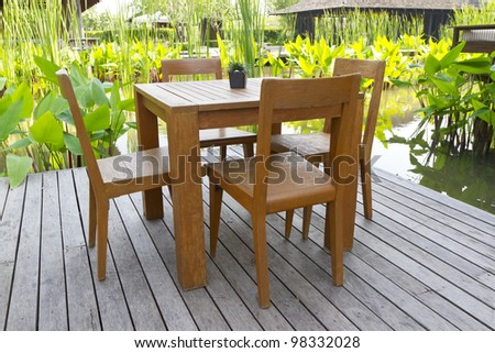wooden table chairs in garden - stock photo