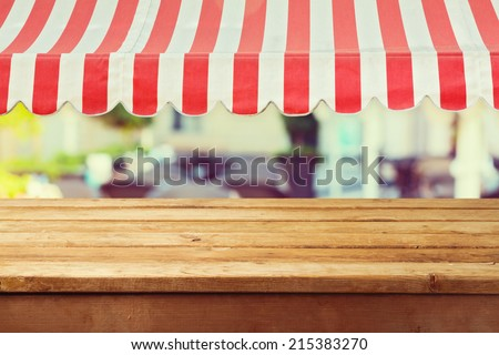 Wooden table counter with awing for product montage display - stock photo