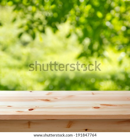 wooden table for background against defocused garden - stock photo