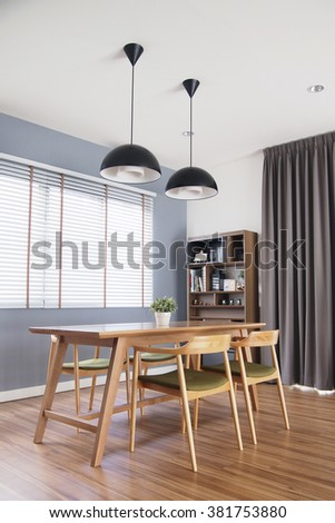 wooden table in cozy dining room with blinds window, decorate, loft style lamps, high cabinet, bookshelf, laminate floor, plant pot, dark grey curtain, perspective view, grey concrete wall - stock photo