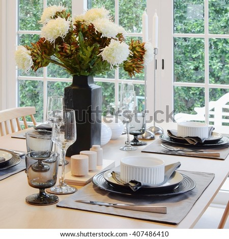 wooden table in dining room with elegant table setting - stock photo