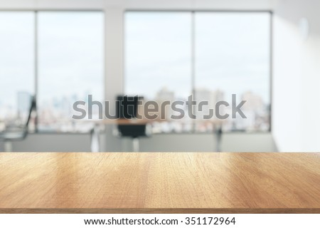 Wooden table in sunny office with big windows - stock photo