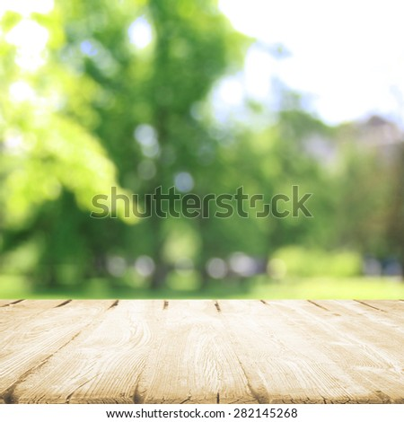 Wooden table in sunny park in summer - stock photo