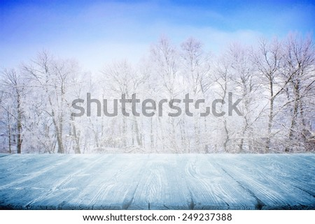 Wooden table in winter field - stock photo