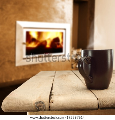 wooden table mug and fireplace  - stock photo