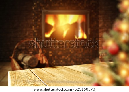 Wooden table of free space fireplace background and blurred xmas tree