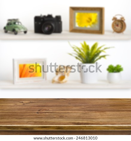 Wooden table on background of shelves with travel objects - stock photo