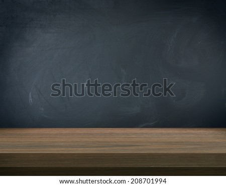 Wooden table on blank blackboard  - stock photo
