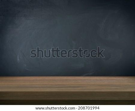 Wooden table on blank blackboard  - stock photo