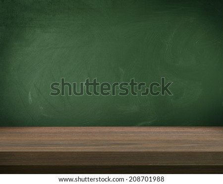 Wooden table on blank green board  - stock photo