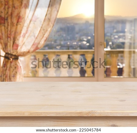 Wooden table on blurred balcony window background - stock photo