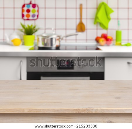 Wooden table on blurred kitchen bench background - stock photo