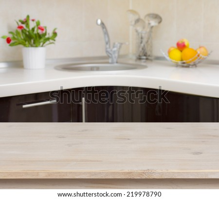 Wooden table on kitchen faucet interior background - stock photo