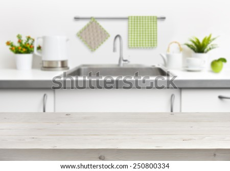 Wooden table on kitchen sink interior background - stock photo