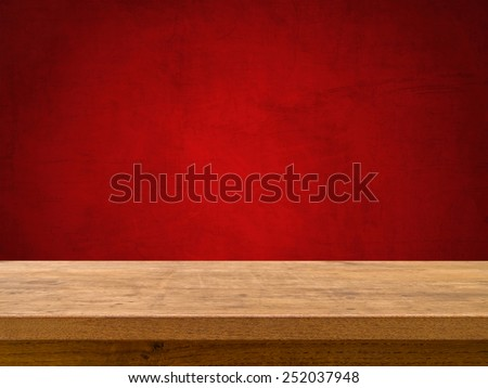 Wooden table on red chalkboard background - stock photo