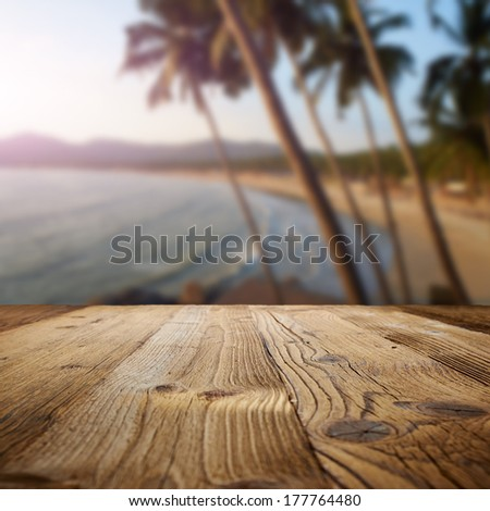 wooden table on the beach with palms - stock photo