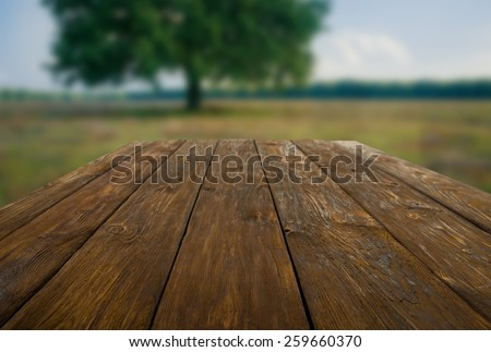 Wooden table outdoors with beautiful summer field and tree background - stock photo