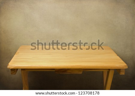 Wooden table over grunge background - stock photo