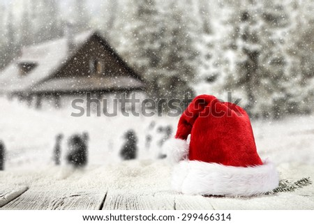 wooden table place of snow and red hat with blurred background  - stock photo