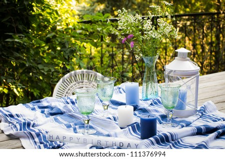 Wooden table served for celebration in blue and white colors with candles, goblets, lamp and flowers in a vase - stock photo