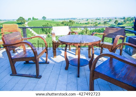 Wooden table set at view point in tea plantation, Thailand