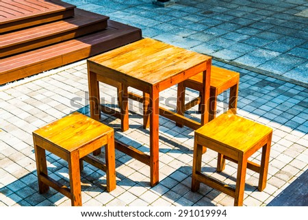 Wooden Table Set on Concrete Block Yard, Thailand. - stock photo